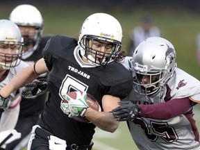 The Thom Trojans' Josh Daly, 5, tries to fight off a tackle from the Johnson Wildcats' Jayson Martin during Regina Intercollegiate Football League action Thursday at Leibel Field.