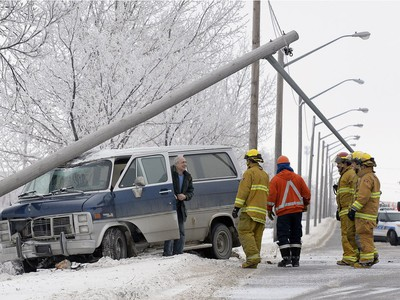 The driver of this van (left) wisely stayed inside until he was told it was safe to exit after sliding into and breaking off a power pole on Ross Ave. east of McDonald Street over the lunch hour Wednesday. He was not hurt in the crash.