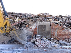 A trackhoe pushes rubble next to the Travellers Building on March 9, 2017.