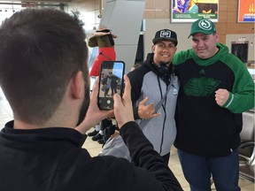 Saskatchewan Roughriders receiver/returner Chad Owens, wearing a black cap, poses for a picture after arriving at Regina International Airport on Monday.