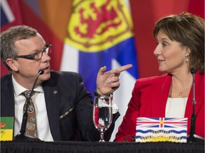 Premier Brad Wall gestures past B.C. Premier Christy Clark during the closing news conference at the First Ministers Meeting in Ottawa, Friday Dec. 9, 2016.