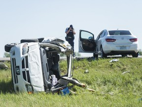 An RCMP member photographs the wreckage of a collision between a car and a minivan north of Regina on Highway 11.
