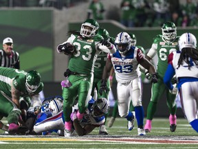 Saskatchewan Roughriders running back Trent Richardson (33) is tackled by Montreal Alouettes linebacker Kyries Hebert (34) during a CFL game held at Mosaic Stadium.