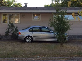 A car parked on a front yard near the University of Regina.