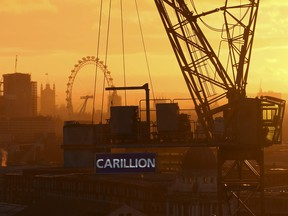 The sun sets behind a crane showing the branding of British construction company Carillion at a building site in central London.