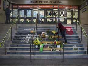 A man drops off flowers at a memorial located inside the Elgar Petersen Arena in Humboldt, SK on Saturday, April 7, 2018.