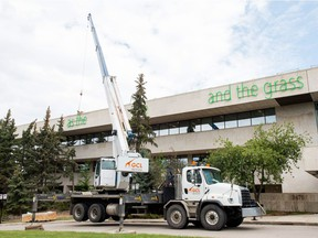 """Workers install a sculpture by artist Duane Linklater, an internationally renowned Canadian artist, on top of the MacKenzie Art Gallery on Albert Street. When finished, the sculpture is to read """"As long as the sun shines, the river flows, and the grass grows."""""""