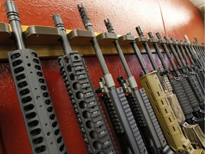 In this file photo, a row of different AR-15 style rifles are displayed for sale. The Ministry of Environment is looking to acquire similar weapons for conservation officers by April 2019.