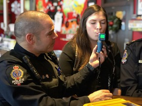 Cst. Marcus Simons with the Regina Police Service demonstrates how to use a roadside alcohol breath tester on volunteer Jennifer Sully, communications officer for SGI during an event to address impaired driving put on by SGI on Dec. 28, 2017.