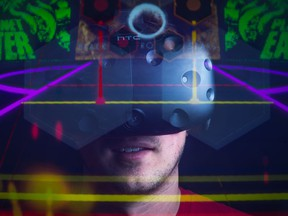 Taylor Eichhorst of BitCutter Studios stands in his home office wearing an HTC Vive virtual reality headset.  The game designer works on games that utilize virtual reality. The game Groove Gunner, which the studio has not yet released, is superimposed over Eichhorst by way of an in-camera double exposure, giving the viewer a look at what he sees when playing the game.