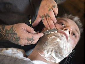 """Jason Zalusky, owner of Bluecore Barber Company, gives Paul Clarke a hot towel straight razor shave in his newly opened shop in Regina. Zalusky is a 3rd generation blue collar worker with his family business J.W. Zalusky & Sons Ltd. 10 years ago the last place Zalusky thought he would be standing would be in his own barber shop. Zalusky says """"After a long uphill battle of travelling the United States for barber school, it is an incredible feeling to see the vision finally all come together 5 years later."""""""
