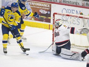 The Saskatoon Blades' Riley McKay, left, can't get the puck past Regina Pats goalie Max Paddock during Friday night's WHL game at the Brandt Centre.