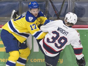 The Saskatoon Blades' Eric Florchuk, 17, gets tied up with Garrett Wright of the Regina Pats in WHL action Friday at the Brandt Centre.