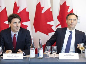 Prime Minister Justin Trudeau (left) sits next to Federal Finance Minister Bill Morneau during a round table discussion at the Canadian Transformational Infrastructure Summit in Toronto on Tuesday May 29, 2018.