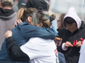 Jackie Wapemoose hugs another woman a gathering to form search parties for her sister Jenaya Wapemoose, a 22-year-old woman who has been missing since March 10th. Beginning at the Esso station on Albert Street and 7th Avenue groups fanned out to put up posters and information.