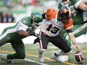 Saskatchewan Roughriders defensive end Charleston Hughes, left, created havoc for the B.C. Lions and quarterback Mike Reilly, 13, on July 20 at Mosaic Stadium.