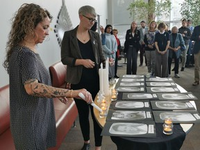 University of Regina Women's Centre executive director Jill Arnott, left, and Regina YWCA senior director of community programs Tara Molson, right, light candles at the U of R in memory of the 14 women killed in the École Polytechnique shooting in Montreal on Dec. 6, 1989.