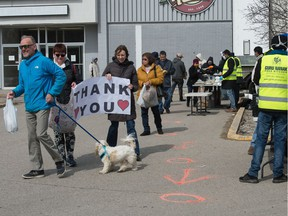 People display a sign of thanks at an event where food was being handed out to those in need by the Sikh community outside the entrance to the Rainbow Cinema on Parliament Avenue in Regina, Saskatchewan.