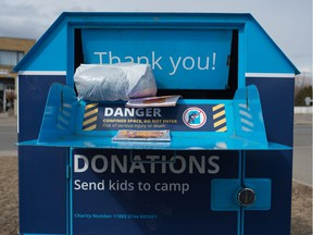 Items hang out of the mouth of a clothing donation bin near a 7-Eleven Store on Montague Street in Regina, Saskatchewan on April 7, 2020. The Diabetes Canada bins are becoming overfull, as pickups have stopped due to the COVID-19 pandemic.