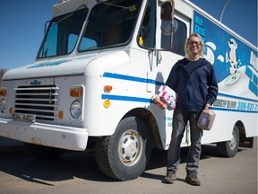 Milkman Kevin Ramstead stands holding milk products in front of one of his delivery trucks on the northwest side of Regina, Saskatchewan on April 9, 2020. Ramstead says he's the city's only remaining door-to-door milkman, but his customer base has recently expanded.