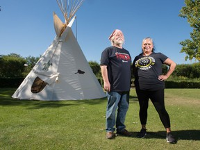 Don Wren, left, and Janna Pratt stand in front of a teepee set up in the park across from the Saskatchewan Legislative Building in Regina, Saskatchewan on Sept. 10, 2020. Both are members of the Unifor 1S Aboriginal and Workers of Colour Committee, which helped organize the set up of the teepee and accompanying learning opportunities provided to visitors.
