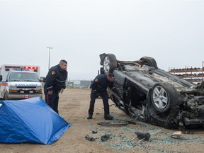 Cst. Raymond Robertson, left, and Cst. Patrick Foster, both of the Saskatoon Police Service, demonstrate a walkthrough of a mock crash scene during an SGI news conference held at the SGI salvage centre in Regina on Oct. 30, 2020.