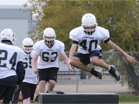 Layne Ermel, 40, takes part in a drill during a Thom Trojans football practice. David Francis, 63, is next in line.