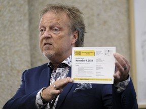 Jim Nicol, chief returning officer for Regina's 2020 municipal/school board elections, shows off a voter information card during a press conference.