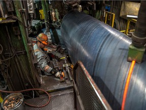 Mike Davis, a mill operator, monitors robotic welders laying beads into a section of pipe in one of the mills at the Evraz steel plant in Regina in April. Workers at the plant working in the tubular division, which manufactures pipe for large scale industrial projects, are facing the prospect of severe layoffs.