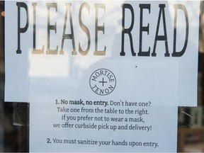 A sign indicating customers must wear masks hangs on the door of Mortise And Tenon in Regina, Saskatchewan on Nov 18, 2020.
