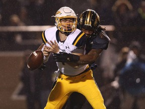 Keion Adams, right, of the Western Michigan Broncos hits quarterback Logan Woodside of the Toledo Rockets and causes a fumble during an NCAA football game on Nov. 25, 2016.