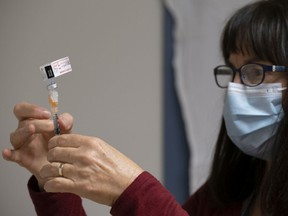 Heather Witzel-Garnhum, nurse clinician, prepares a syringe with the Pfizer-BioNTech COVID-19 vaccine at the Regina General Hospital in Regina on Tuesday Dec. 15, 2020. More than 200 vaccinations are planned for Dec. 16.