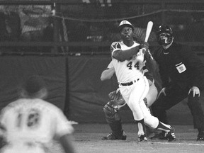 Atlanta Braves' Hank Aaron eyes the flight of the ball after hitting his record-setting 715th career homer in a Major League Baseball game against the Los Angeles Dodgers on April 8, 1974. Dodgers pitcher Al Downing and umpire David Davidson look on. Aaron died Friday at 86.