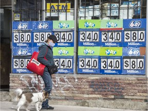 A pedestrian wearing a mask and walking her dog walks past Lotto Max and Lotto 649 advertising on Toronto's Broadview Avenue during the Covid 19 pandemic, Tuesday October 20, 2020.