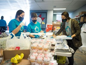 From left, Chasity Delorme, Cara Spence and Cody Lloyd fill styrofoam containers with food for memorial feast for Derrick Sasakamoose, which was held at the Awasiw Warming Shelter on 5th Avenue in Regina, Saskatchewan on Feb. 13, 2021.