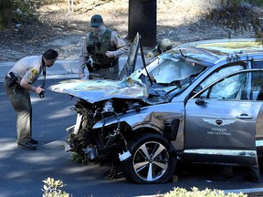 Los Angeles County Sheriff's Deputies inspect the vehicle of golfer Tiger Woods after it was involved in a single-vehicle accident in Los Angeles February 23, 2021.