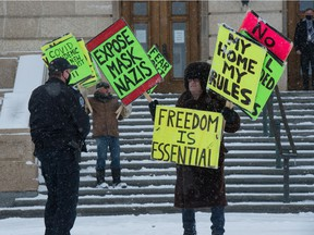An anti-mask demonstrator has words with a peace officer at the Saskatchewan Legislative Building in Regina, Saskatchewan on Mar. 9, 2021. Police say the majority of interactions are peaceful, but their enforcement targets leaders and organizers as a means of deterrence.