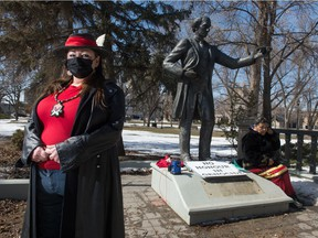 Star Andreas stands near the John A. Macdonald statue in Victoria Park in Regina, Saskatchewan on March 31, 2021. Regina's city council is discussing the future of the statue and Andreas was at the statue waiting to be called into the council meeting remotely, to speak as a delegate. A small speaker can be seen at the foot of the statue. Andreas had her phone connected to the speaker to hear when she was called upon during the meeting.