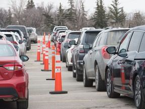 Motorists wait for COVID-19 testing last week on the Evraz Place grounds.