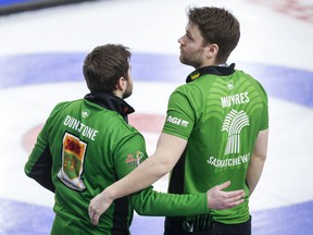 Team Saskatchewan skip Matt Dunstone, left, and second Kirk Muyres comfort each other after Sunday's heartbreaking loss to Alberta's Brendan Bottcher in the Brier semi-final.