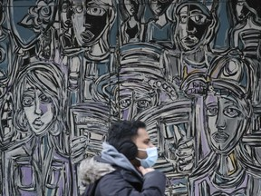 A masked pedestrian walks past a mural in downtown Regina on March 24, 2021. A day earlier, the provincial government announced new restrictions in an effort to limit rising COVID-19 numbers in the city.