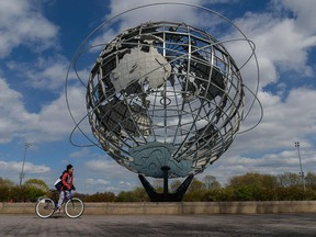A boy rides his bike past the Unisphere, a stainless steel representation of the Earth, in Flushing Meadows Corona Park on Earth Day, April 22, 2021 in New York City.