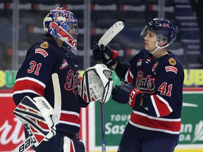 Regina Pats defenceman Ryker Evans (41) congratulates goaltender Roddy Ross (31) after a 6-1 victory over the Current Broncos on April 6, 2021 at the Brandt Centre. Keith Hershmiller Photography.