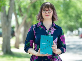 """Courtney Bates-Hardy, associate poetry editor of the new book """"apart: a year of pandemic poetry and prose,"""" holds a copy of the book near her home in Regina, Saskatchewan on July 2, 2021. BRANDON HARDER/ Regina Leader-Post"""
