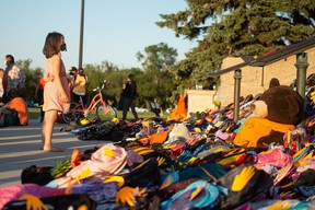 A young girl looks at a collection of children's backpacks on the steps of the Saskatchewan Legislative Building during a vigil event, pertaining to the Cowessess and Kamloops discoveries, held there in Regina, Saskatchewan on July 1, 2021.