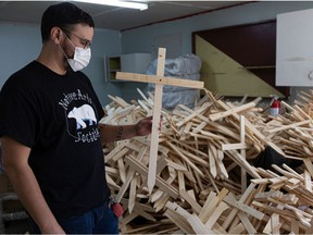 Jason Mercredi holds one of hundreds of crosses made to commemorate victims of fatal overdoses.