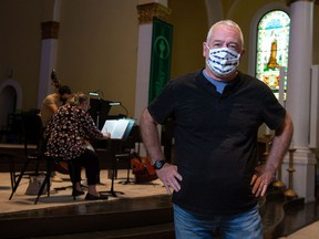 Regina Symphony Orchestra executive director Mike Forrester stands in front of a group of musicians during a rehearsal at the Holy Rosary cathedral on Sept. 14, 2021.