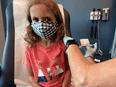A seven-year-old girl is inoculated with a reduced dose of the Pfizer-BioNTech COVID-19 vaccine during a trial at Duke University in Durham, North Carolina on September 28, 2021.
