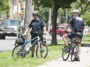 Two police officers on bikes stand on Queens Avenue between Adelaide and William Streets. (File photo)