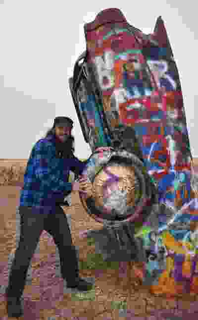 Mike from Milwaukee, Wisc.  takes a break from a road trip to Los Angeles to check out the 10 half-buried Caddies at Cadillac Ranch, outside Amaraillo, Texas. Mike spray-painted his name on the quirky installation about 10 years earlier.  BARBARA TAYLOR/The London Free Press/Postmedia News